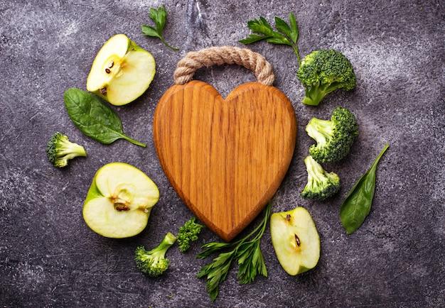 Groene voedselachtergrond met houten raad in vorm van hart