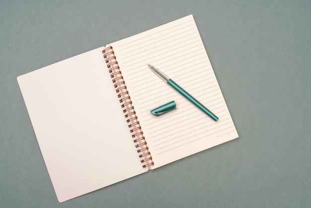 Groene vulpen en notitieblokpagina's. voorbereiding op studiebeurs en onderwijs. de kwelling van creativiteit.