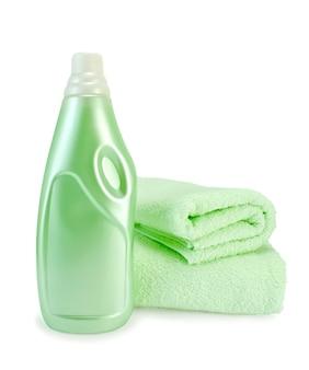 Groene wasverzachter in de fles en twee groene handdoeken geïsoleerd