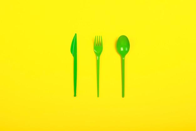 Groene wegwerp plastic servies en apparaten voor het voedsel op een gele achtergrond. vork, lepel en mes. concept plastic, schadelijk, milieuvervuiling, stop plastic. plat lag, bovenaanzicht.
