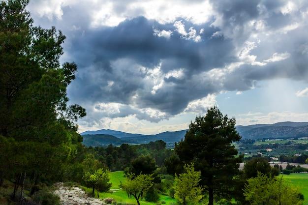Groene weide in een dag met witte en grijze wolken en zonnestralen met bergen op de achtergrond.