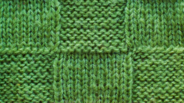 Groene wol van gebreid garen, close-up van de textuur het patroon gebreide stof