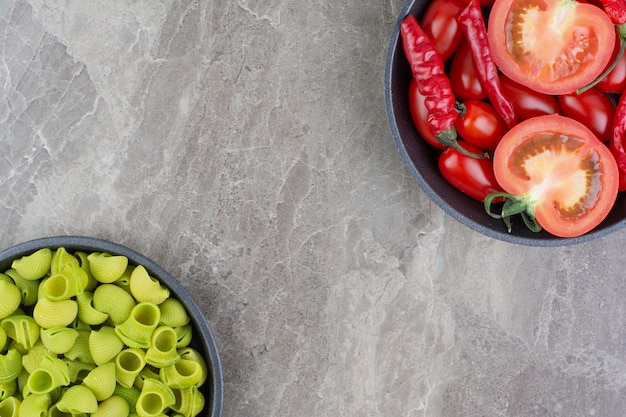 Groene zelfgemaakte pasta's met chilipepers en tomaten.