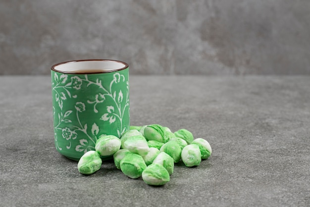 Groene zoete snoepjes met een kopje lekkere thee