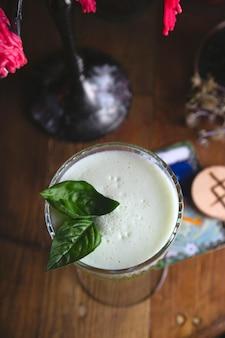 Groene zure cocktail met basilicum onder rode kaarsen in het restaurant van de mysterieuze heks