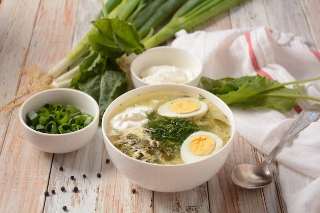 Groene zuring en spinaziesoep met gekookt ei, bosui en zure room