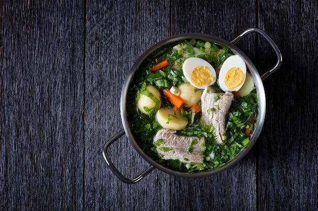 Groene zuring soep met peterselie en groene ui met varkensribbetjes, met vleesbouillon en hardgekookte eierhelften, geserveerd op een metalen bouillonpot op een donkere houten tafel, van bovenaf bekeken, kopie ruimte