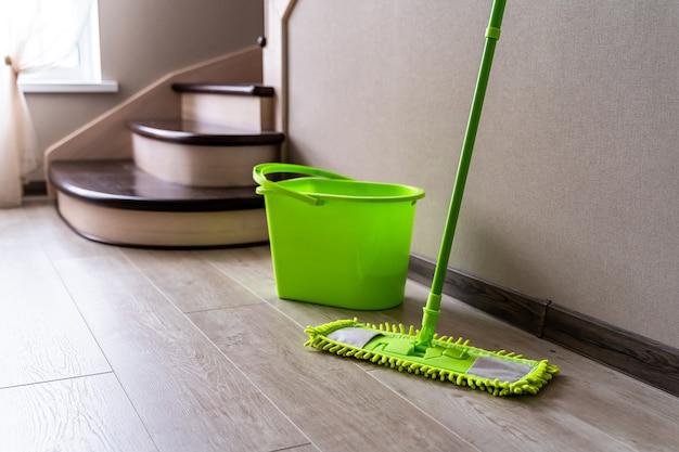 Groene zwabber die zich dichtbij witte muur bevindt. schoonmaak spullen. groene plastic emmer. huishouden.