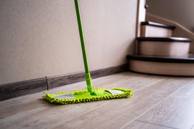 Groene zwabber die zich dichtbij witte muur bevindt. schoonmaak spullen. huishouden.