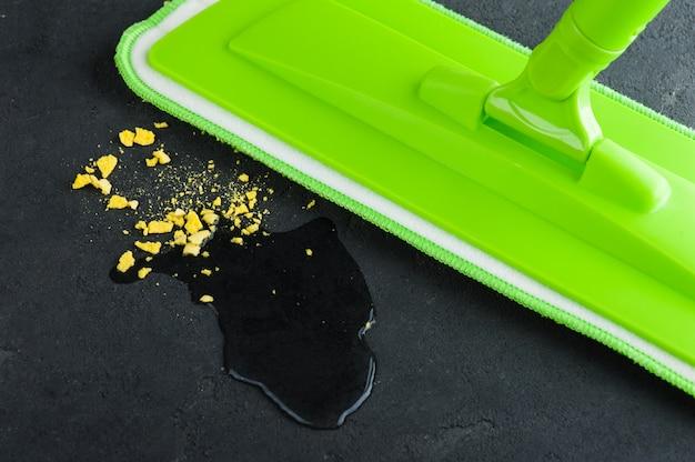Groene zwabber die zwarte concrete vloer dweilen