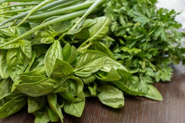 Groenen, basilicum, peterselie, ui close-up op tafel
