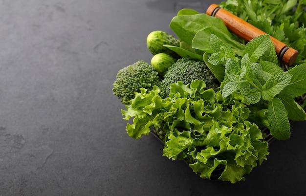 Groenen: spinazie, komkommer, broccoli, knoflook, munt, peterselie, sla, ui op een zwarte achtergrond