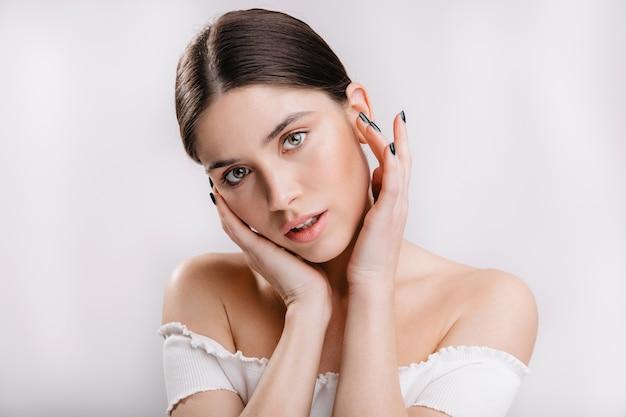 Groenogig jong vrouwelijk model zonder make-up die sensueel op witte muur kijken.