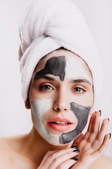Groenogig meisje doet kuuroord gezichtsprocedure op witte muur. portret van vrouw in handdoek met kleimasker.