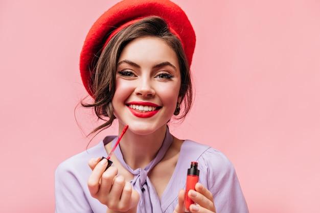 Groenogig meisje met sneeuwwitte glimlach schildert haar lippen met rode lippenstift. portret van dame in stijlvolle baret op roze achtergrond.