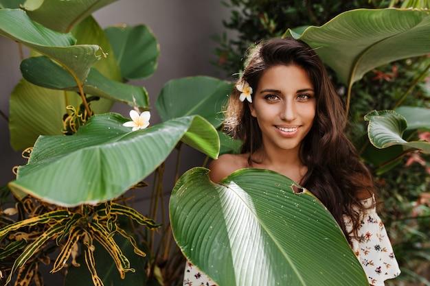 Groenogige brunette vrouw met bloem in haar haar kijkt naar voren, poseren tussen grote bladeren van tropische plant