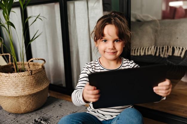 Groenogige kleine vrouw in de gestreepte tablet van de sweaterholding en camera met glimlach bekijkt.