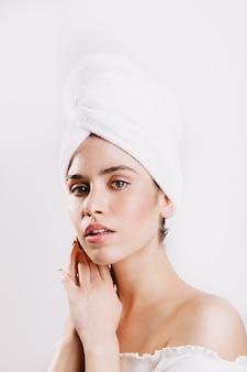 Groenogige vrouw met perfecte huid die zich voordeed op witte muur met handdoek op haar hoofd.