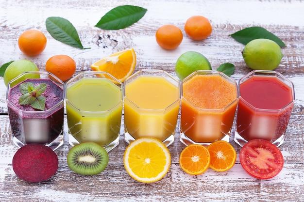 Groente- en citrusvruchtensappen stukken groenten en fruit op houten bureau ongebruikelijk bovenaanzicht