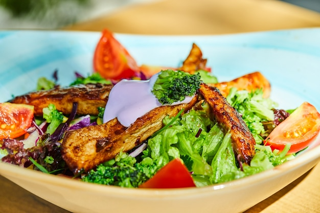 Groente- en kipsalade op blauw bord