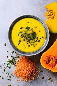 Groente en linzen romige soep, gesneden pompoen, zaden, peterselie op lichtgrijs.