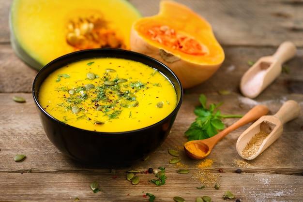 Groente en linzen romige soep, gesneden pompoen, zaden, peterselie op rustieke houten.