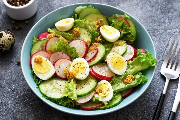 Groente, frisse salade met radijs, ei en slablaadjes in een blauw bord op een betonnen achtergrond.