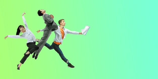 Groente. gelukkige kantoormedewerkers springen en dansen in casual kleding of pak geïsoleerd op gradiënt neon vloeistof achtergrond. business, start-up, werkende open ruimte, beweging, actieconcept. creatieve collage.