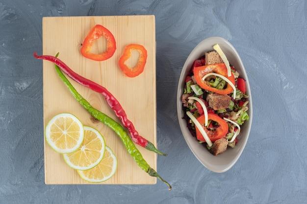 Groente salaed naast een houten bord met chili pepers en plakjes citroen en paprika op marmeren tafel.