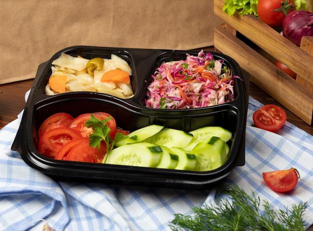 Groente, tomaat komkommer salade afhaalmaaltijden met gemarineerde kool