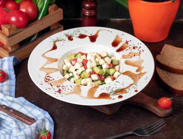 Groente, tomaten, komkommer, rokasalade. salade met sumakh en citroen op de keukentafel in witte plaat