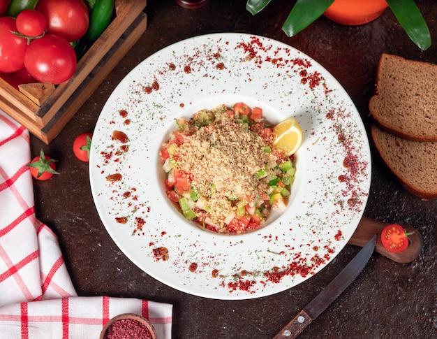 Groente, tomaten, komkommersalade met crackers. salade op de keukentafel met sumakh en citroen in witte plaat