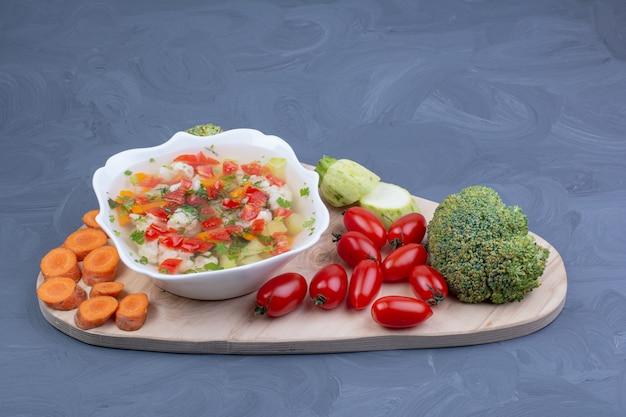 Groentebouillon soep in een witte kom met gehakt voedsel