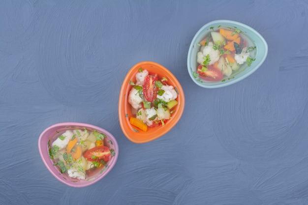 Groentebouillon soep in kleurrijke kopjes op blauw.