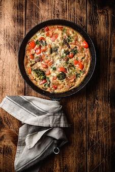 Groentefrittata met broccoli, rode paprika en kruiden in gietijzeren koekenpan. uitzicht van boven