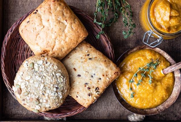 Groentekaviaar in potten, verse tomaten, ui, wortel, aubergines en tijm geserveerd met brood in een houten dienblad.