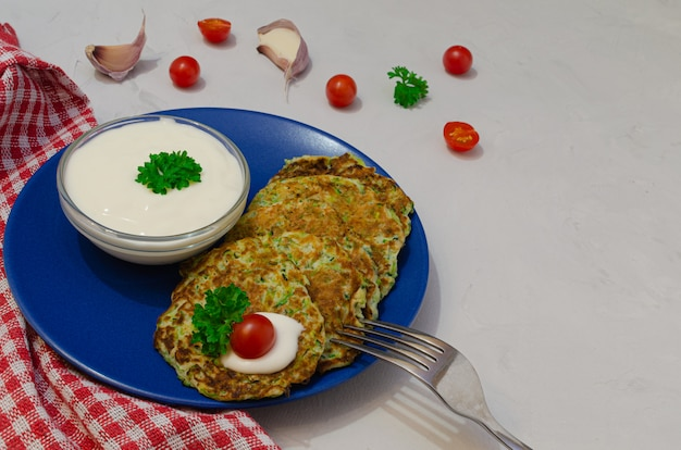 Groentekoteletten van courgette met knoflook, kerstomaatjes en yoghurtsaus. bovenaanzicht