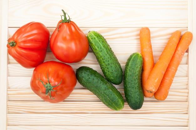 Groenten achtergrond. tomaten coeur de boeuf, komkommers en wortels
