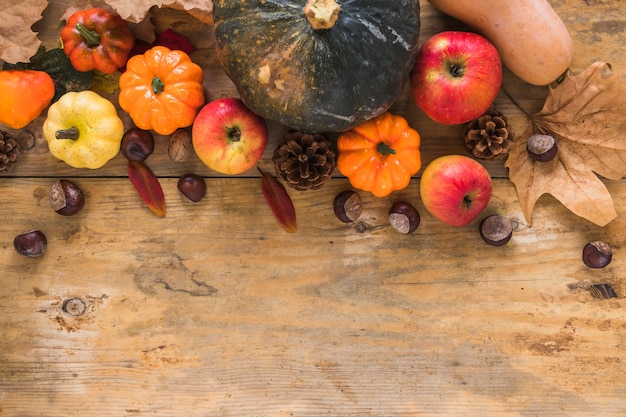 Groenten en droge bladeren op houten bord