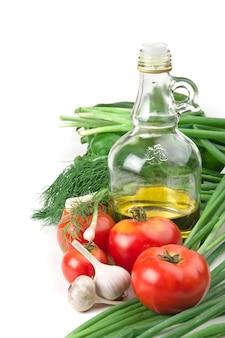 Groenten en een fles olie, stilleven dat op wit wordt geïsoleerd