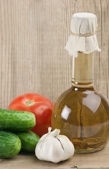 Groenten en een fles olie, stilleven op een houten tafel
