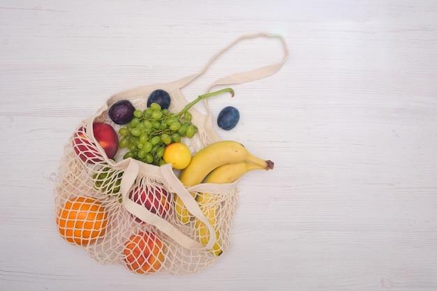 Groenten en fruit in een netzak op een houten achtergrond