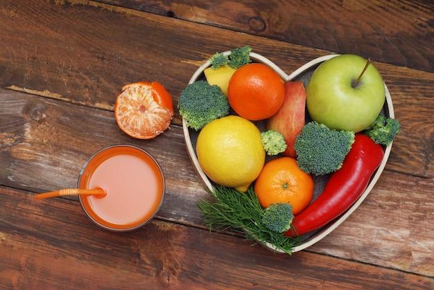 Groenten en fruit in hartvormige houten kist. broccoli, appels, peper, mandarijnen.
