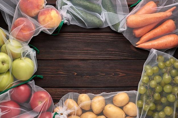 Groenten en fruit in herbruikbare milieuvriendelijke zakken op houten achtergrond. zero waste. kopieer ruimte