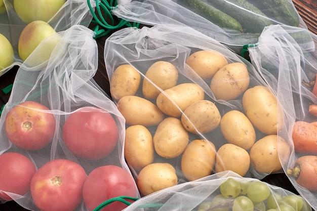 Groenten en fruit in herbruikbare milieuvriendelijke zakken op houten achtergrond. zero waste.