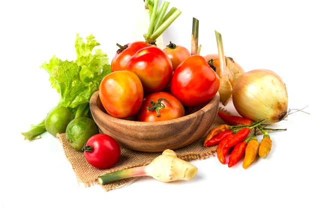 Groenten en fruit in houten kom op witte achtergrond, tomaat, citroen, spaanse peper