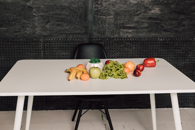 Groenten en fruit liggen op een witte tafel