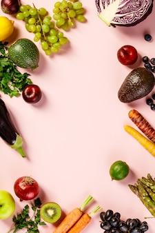 Groenten en fruit op roze tafel achtergrond, bovenaanzicht