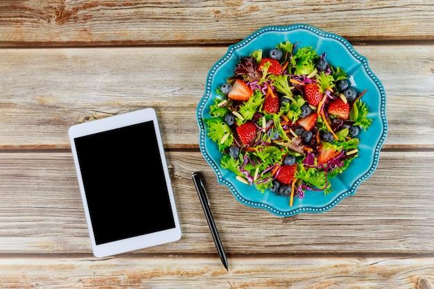 Groenten en fruit salade met tablet op houten tafel
