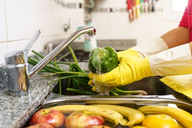 Groenten en fruit schoonmaken met latex handschoenen voor coronavirus